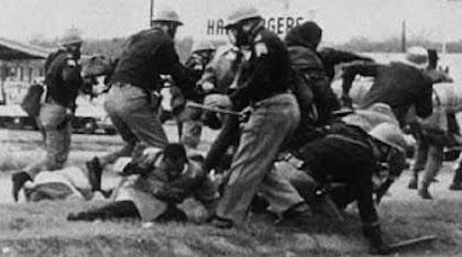 Alabama state troopers attacking John Lewis at the Edmund Pettus Bridge.