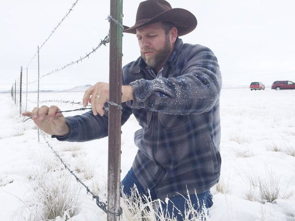 Ammon Bundy poses for the cameras to tear down a barbed-wire fence separating federal and private land.