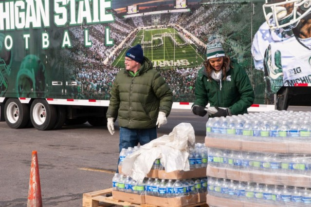 The Michigan State University football trailer delivered flats of bottled water to residents of Flint, Michigan, and picked up empty bottles at the same time. Student and community volunteers are taking part in the plastic bottle recycling effort as well as the water distribution. (Photo courtesy of Carolyn Kennedy and Schupan Recycling)