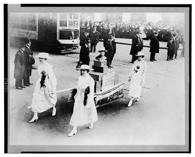 Women carrying ballot boxes on a stretcher during a suffrage parade on Oct. 23, 1915, in New York City. Those scowling men glaring at the suffragists had no idea what they were up against. (Library of Congress Prints and Photographs Division)
